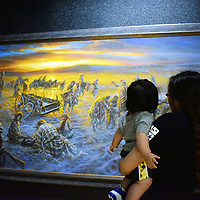 Jessica Norton, 20, of Pueblo Pintado holds her son Anthony Blackbird while looking at a painting of the Long Walk by Shiprock artist James King during Treaty Day celebrations in Window Rock Friday. The painting is on a special display in commemoration of Treaty Day and remembrance of the Long Walk at the Navajo Nation Museum in Window Rock, Arizona.