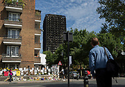 Twelve days after the devastating fire that killed an unspecified number of people in Grenfell Tower, bystanders stop to gaze up at the charred tower block which remains a crime scene, on 26th June 2017, in the London borough of Kensington & Chelsea, England.
