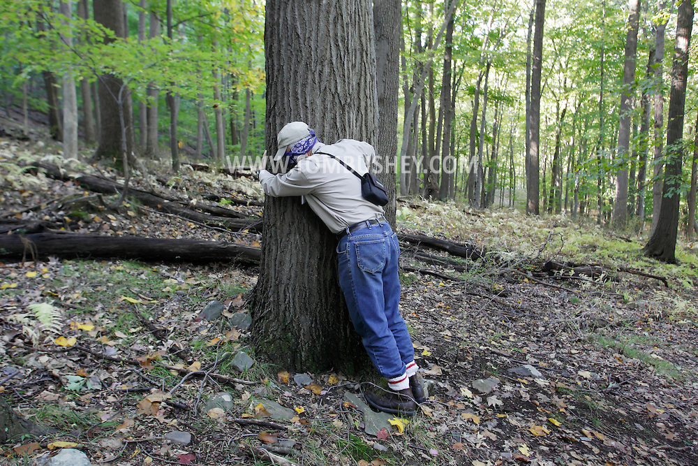 Salisbury Mills, New York - George Muser of the Hudson Highlands Nature Museum hugs a tree while blindfolded during an exercise about the senses on a hike with a group through Clove Brook Farm at the base of Schunnemunk Mountain on Oct. 2, 2010. The outing was organized by the Hudson Highlands Nature Museum.