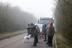 Denham, UK. 6 February, 2020. An environmental activist waves through local traffic as a truck delivering fencing and other supplies to be used for works associated with the HS2 high-speed rail link close to the river Colne at Denham Ford is delayed for several hours by activists from Save the Colne Valley, Stop HS2 and Extinction Rebellion walking at a snail's pace along the road in front of it.