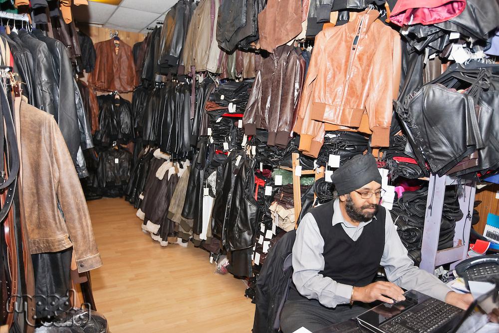 Man working on laptop at clothing shop