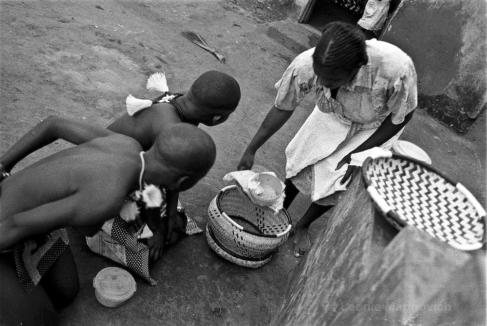 IPLM0043 , South Africa, Venda, June 2001. Girls attending the initation or coming-of-age ceremony of the Tshivhase royal dynasty. They come out during the day, to take food to their families. Everytime they come across older women, they have to fall down and wait for the woman to allow them to continue.