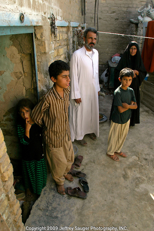 Hassan Atshan Nassar poses with his family in their one-room home attached to the back of an elementary school in the modernized center of the village Suq ash Shuyukh, about 20 miles southeast of Nasiriyah, Iraq, Sunday, August 3, 2003. He is a security guard at the school and earns $60 USD/month. Before Saddam Hussein was toppled, he earned about $10/month...Since the 1991 uprising against Saddam Hussein in Shiite dominated Southern Iraq, people of this area have suffered greatly through his methods of disrupting daily life. For example, modernization came to a hault as money was diverted to Baath Party strongholds. Check points on on every other corner made it nearly impossible to go to work, the doctor, or visit family. Teachers made $5 U.S. per month and had to spend almost all of their salary for taxis in order to go to work...He tried to kill the people by cutting off the rivers that village survival depends on. Dams and canals dirverted the fresh water from flowing into the swamps by way of tributaries. In effect, without fresh water flowing in, the people started poisoning the water supply themselves by using it to wash and clean. Their primitive sewers still flow freely into the same waters that animals use and that feed their rice fields.
