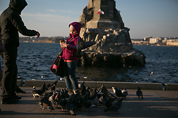 A girl feeding birds in the waterfront of Sevastopol three days before the referendum. Ukraine , Thursday, 13th March 2014. Picture by Daniel Leal-Olivas / i-Images