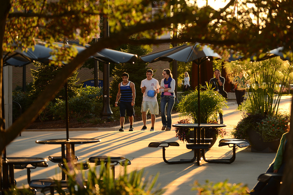 Three students walk through the Risman Plaza on a warm fall evening. The Risman Plaza is a main gathering place for students.