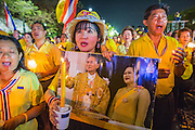 05 MAY 2104 - BANGKOK, THAILAND:  Supporters of the Thai monarchy sing the King's Anthem by candlelight during a vigil for the King on Sanam Luang. Thousands of Thais packed the area around Sanam Luang and the Grand Palace Monday evening for a special ceremony to mark Coronation Day, which honored the 64th anniversary of the coronation of Bhumibol Adulyadej, the King of Thailand. Many of the people also support the anti-government movement led by Suthep Thaugsuban. Most of the anti-government protesters are conservative supporters of the monarchy.   PHOTO BY JACK KURTZ