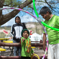 Maddix Peshlakai, left plays a ring toss game with help from volunteer Vern Thomas at the Zoo Fest event held at the Navajo Nation Zoo in Window Rock Saturday.
