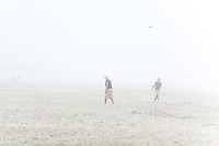 Two men playing frisbee on the foggy beach near Newport, Oregon.