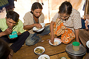 "25 FEBRUARY 2008 -- MAE SOT, TAK, THAILAND: Burmese migrant workers eat their lunches during their break on a commercial rose growing farm near Mae Sot, Thailand. There are millions of Burmese migrant workers and refugees living in Thailand. Many live in refugee camps along the Thai-Burma (Myanmar) border, but most live in Thailand as illegal immigrants. They don't have papers and can not live, work or travel in Thailand but they do so ""under the radar"" by either avoiding Thai officials or paying bribes to stay in the country. Most have fled political persecution in Burma but many are simply in search of a better life and greater economic opportunity.  Photo by Jack Kurtz"