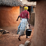 A resident of the Gambaga camp for alleged witches carries water from the communal tap her hut.