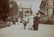 young boy with two adult woman strolling in a public park France early 1900s