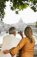 Couple on bridge photographing cathedral in Rome Italy back view