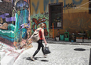 A woman walks through an alley lined with street art in Cerro Alegre, Valparaiso.