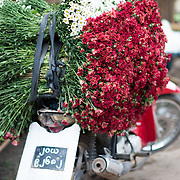 A motorbike is loaded up with fresh flowers for delivery at the afternoon flower street market in Mandalay, Myanmar (Burma).