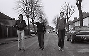 Three friends walk down the middle of a  suburban back street. London, Greenford, UK, 1980s.