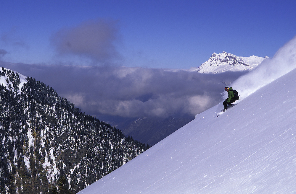 A snowboarder gets first tracks on the upper slopes of Champex Lac switzerland