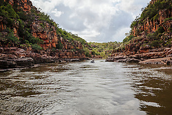 A small dinghy travels down the Sale River in the Kimberley wet season.