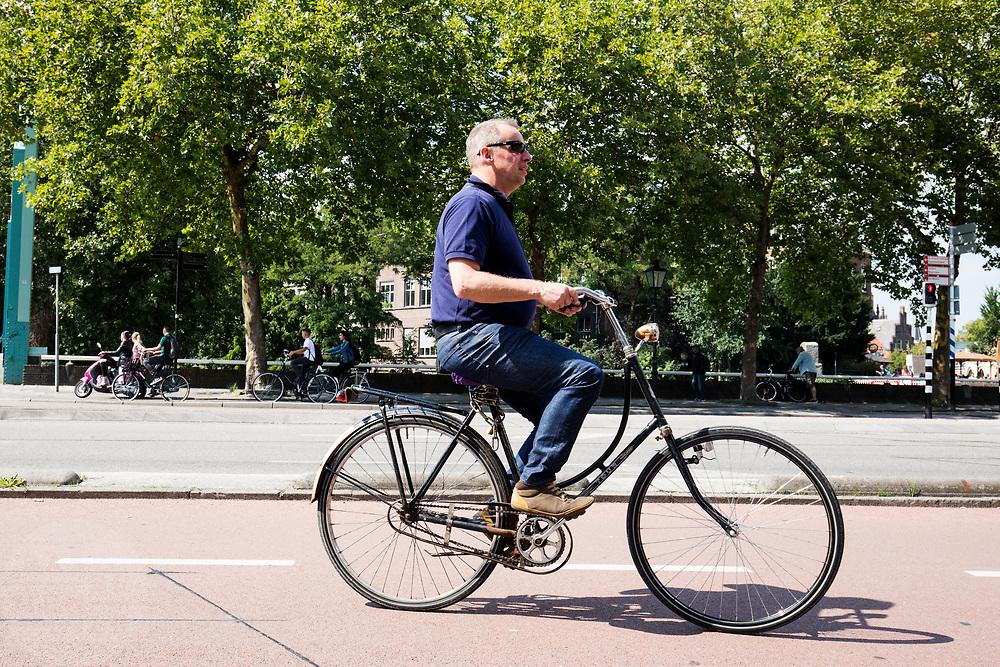 In Utrecht rijdt een man op een oude damesfiets door de binnenstad.<br /> <br /> In Utrecht cyclist ride at the city center.