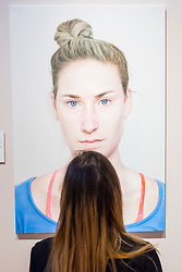 Edinburgh, Scotland, United Kingdom. 14 December, 2017. <br /> Jill Brown, Press and Marketing Officer at National Galleries Scotland looks at painting Simona by Lukas Betinsky  at the exhibition of BP Portrait Award 2017.<br /> The BP Portrait Award 2017 opens at the Scottish National Portrait Gallery on 16 December 2017.