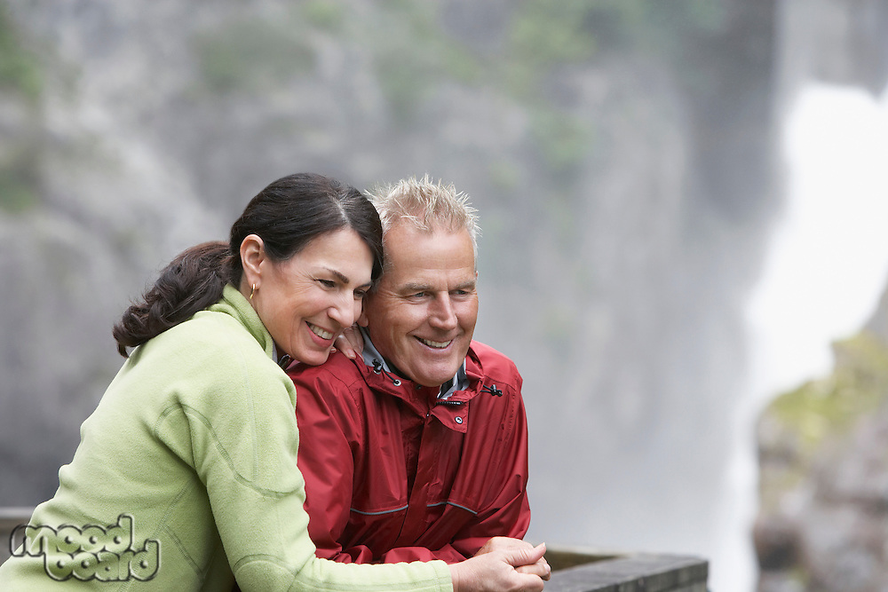 Man and woman in mountains looking down smiling