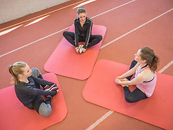 Three young women practicing yoga in athletics hall on tartan track, Offenburg, Baden-Wuerttemberg, Germany