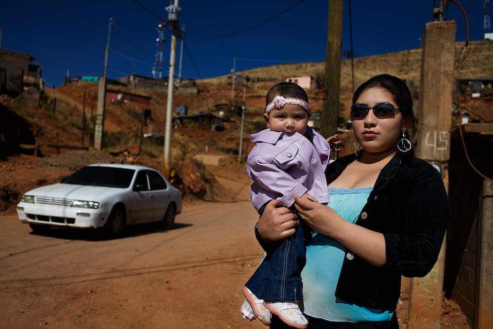 A woman stands with her baby and waits for the bus in a poor , dangerous neighborhood in Nogales.  Locals say drug and people smugglers live in these neighborhoods.