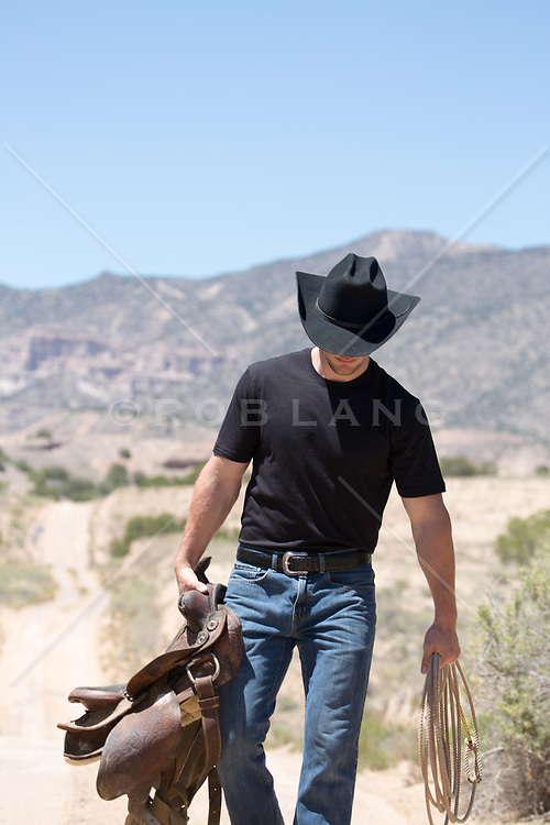 cowboy walking down a dirt road carrying a saddle in his hand