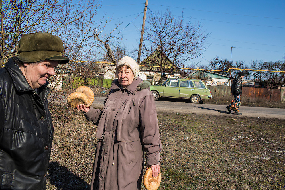 MARIINKA, UKRAINE - FEBRUARY 20, 2016:  Local residents hold bread distributed as humanitarian assistance by volunteers affiliated with the Christian Help Center of the Church of the Transfiguration in Mariinka, Ukraine. The Donetsk suburb has been the scene of some of the heaviest fighting recently between Ukrainian forces and pro-Russian rebels. CREDIT: Brendan Hoffman for The New York Times