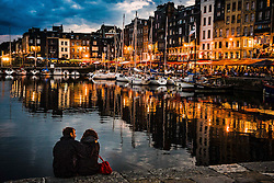A couple sit by the harbour in the evening in Honfleur, Normandy, France