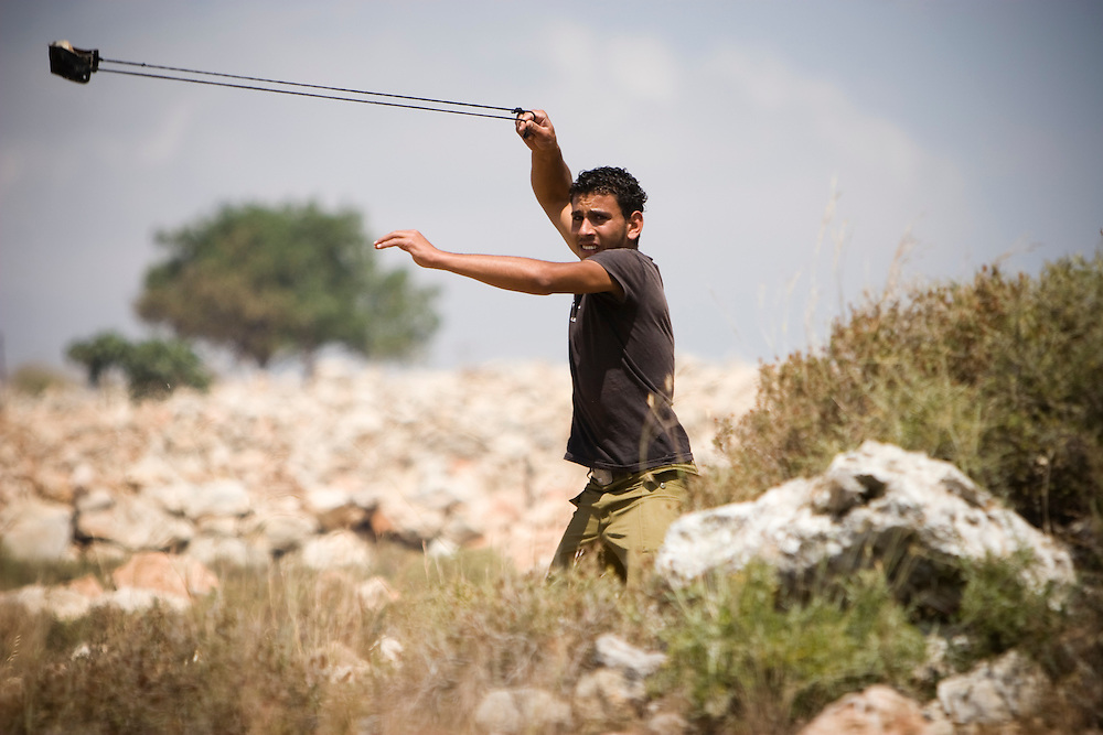 A Palestinian youth launches stones at Israeli soldiers who in turn fire on the protesters with rubber bullets and tear gas in the West Bank village of Bil'in. May 2008
