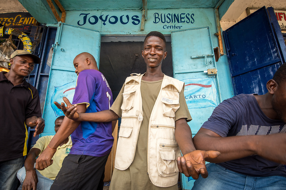 A group of men gather around the front of a business center. Ganta Liberia