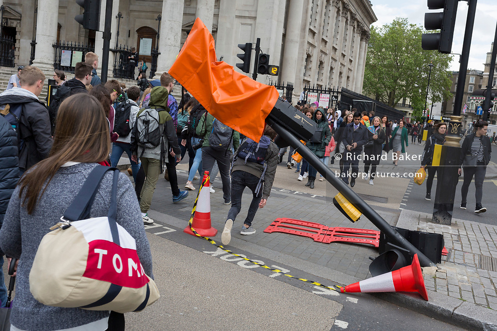During seasonal spring rain, a pedestrian ducks under a leaning traffic light post, damaged after a recent vehicle crash, on 9th May 2019, in London, England.