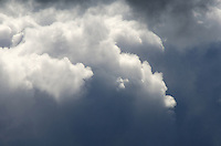Cumulonimbus storm clouds lit from above with sunlight and dark below.