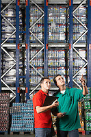 Two Men standing side by side gesturing in warehouse with full shelves