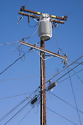 a typical American electricity and phone wire pole in a residential area