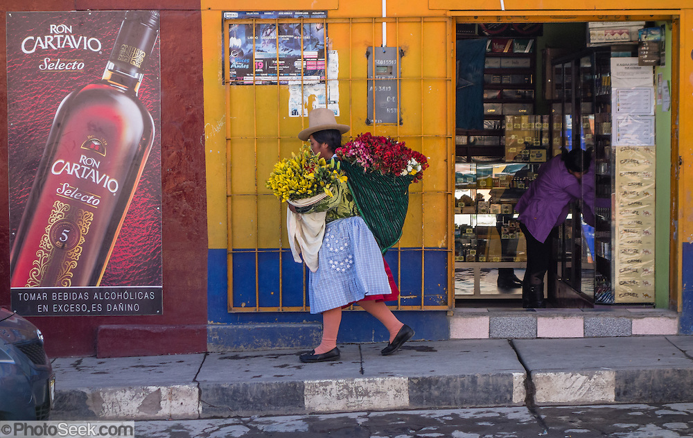 A woman carries large sacks of yellow and red flowers on a street in Huaraz, in the Santa Valley (Callejon de Huaylas), Ancash Region, Peru, Andes Mountains, South America.