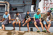 "10 JUNE 2014 - YANGON, MYANMAR:   Stevedores wait to go to work offloading 110 pound (50 kilo) sacks of fish meal from a river freighter on the banana jetty. The ""banana jetty"" is on the Yangon River north of central Yangon on Strand Road. Bananas, coconuts and other fruit are brought in here from upcountry, sold and reshipped to other parts of Myanmar (Burma). All of the labor here is done by hand. Porters carry the produce to the jetty and porters load the boats before they steam upriver.   PHOTO BY JACK KURTZ"