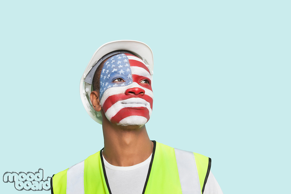 Young architect with American flag painted on face against colored background