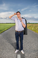 Full length of tired young man standing on empty rural road