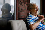 """Achille (Kelly) Gasbarra, sits on his front porch in New Kensington, Pa. Gasbarra, who recently celebrated his 75th wedding anniversary with his wife, was drafted into the Navy as a cook in 1943. He claims to be """"the only guy in the Navy that never saw water,"""" sinces he worked in Nevada at a naval ammunition depot.<br /> <br /> New Kensington, a small city located twenty miles northeast of Pittsburgh, is known as the """"Birthplace of the Aluminum Industry"""" since it was where the Aluminum Company of America's (ALCOA) first facility was built in 1891. ALCOA presence drove the area's economy for over sixty years.<br /> <br /> When ALCOA closed its New Kensington operations in 1971, 3,300 jobs were lost – a fifth of the local population. As a result,  property values rapidly declined and many homeowners became underwater on their mortgages.<br /> <br /> The population shrank nearly in half, from 26,000 in the early 1970s to about 14,000. Businesses moved to malls or suburban commercial strips and the buildings that previously housed them fell into decay and the city's tax revenues plummeted."""