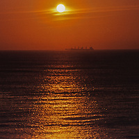 Sunrise over sea with distant freighter