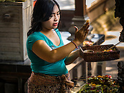 10 OCTOBER 2016 - UBUD, BALI, INDONESIA: People pray in the temple in the market in Ubud. The morning market in Ubud is for produce and meat and serves local people from about 4:30 AM until about 7:30 AM. As the morning progresses the local vendors pack up and leave and vendors selling tourist curios move in. By about 8:30 AM the market is mostly a tourist market selling curios to tourists. Ubud is Bali's art and cultural center.      PHOTO BY JACK KURTZ