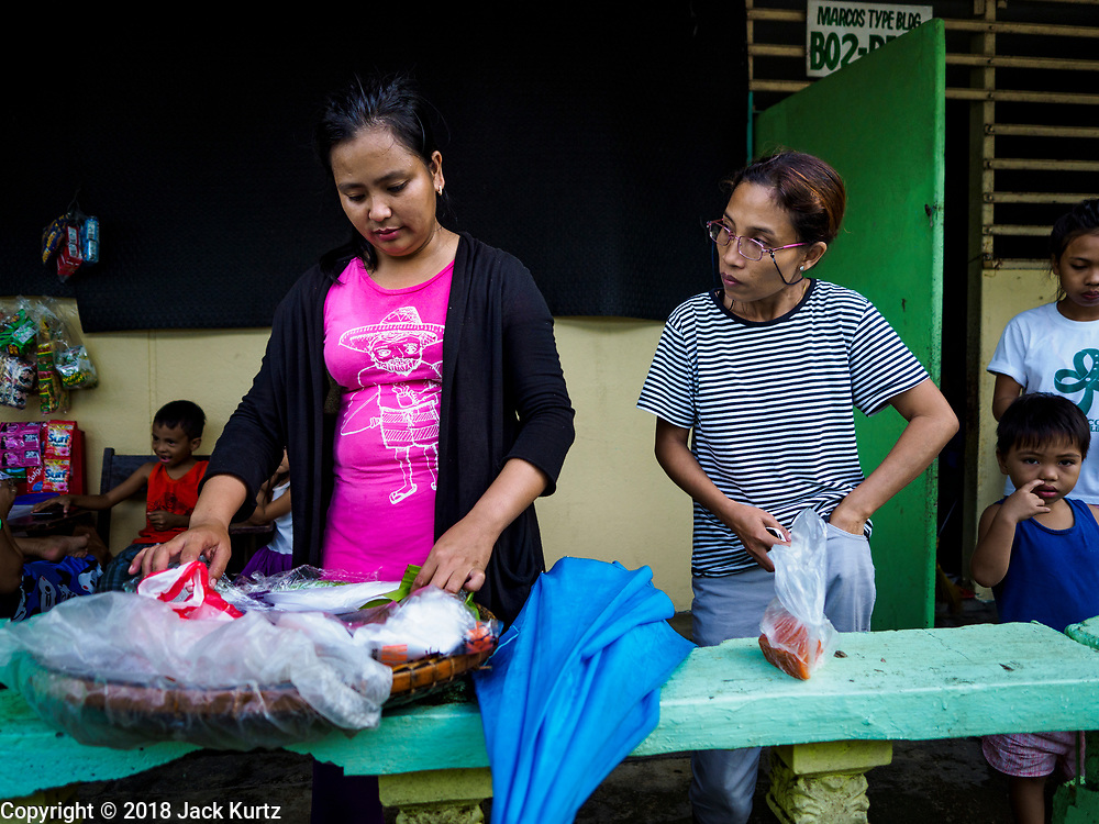"""20 JANUARY 2018 - CAMALIG, ALBAY, PHILIPPINES: A """"sapin sapin"""" vender (a Filipino snack made from rice and coconut milk) sells the snack to evacuees at the Barangay Cabangan evacuee shelter in a school in Camalig. There are about 650 people living at the shelter. They won't be allowed to move back to their homes until officials determine that Mayon volcano is safe and not likely to erupt. More than 30,000 people have been evacuated from communities on the near the Mayon volcano in Albay province in the Philippines. Most of the evacuees are staying at school in communities outside of the evacuation zone.  PHOTO BY JACK KURTZ"""