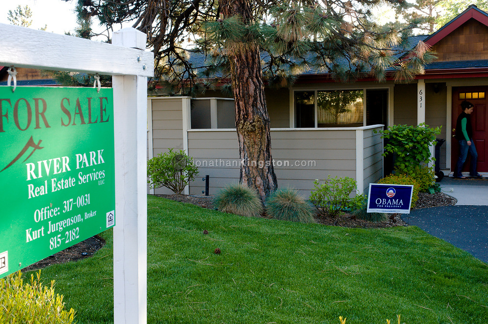A for sale sign in front of a house with an Obama poster and a young woman walking out of the door in Bend, Oregon. (releasecode: jk_mr1032)