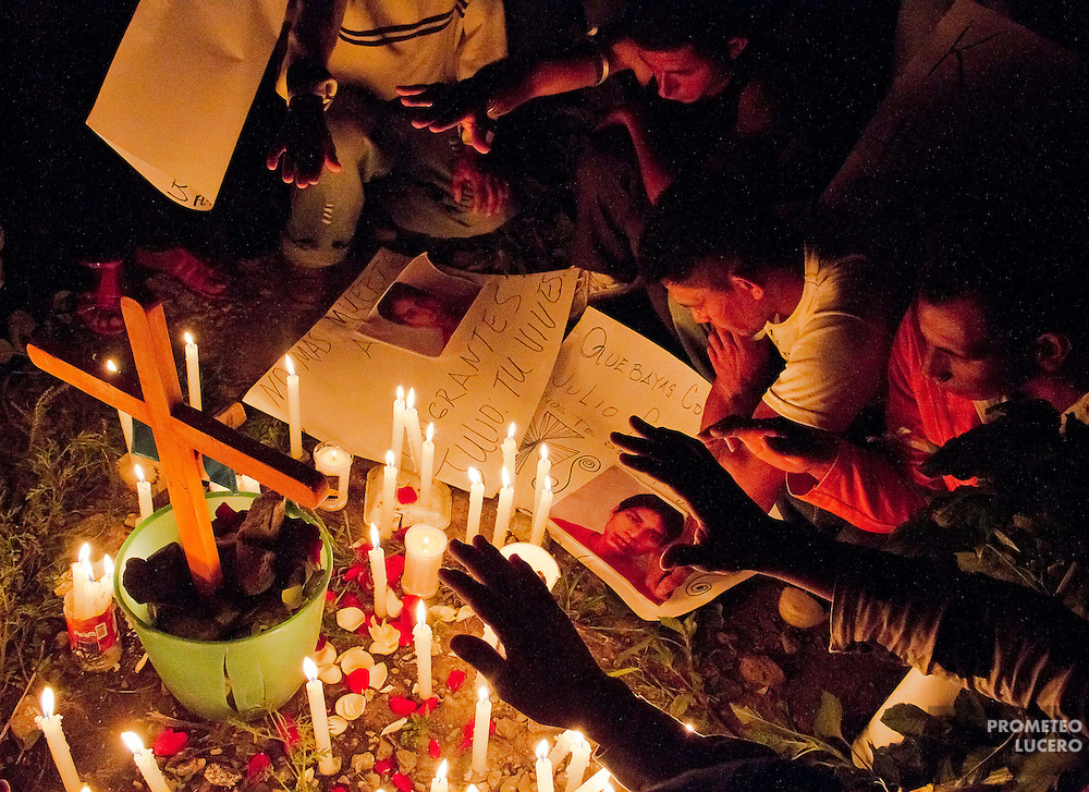 "Migrants pray near the place where guatemalan indigenous migrant Julio Fernando Cardona Agustín was murdered in Lechería, Estado de México. Cardona was arrested by police hours before his body was found dead and arrived with the caravan ""Paso a paso por la paz"" (Step by step for peace) (Photo: Prometeo Lucero)"