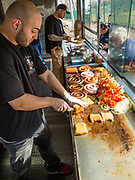 Anthony Bonilla, owner Gary D'Angelo's nephew, slicing a knish in the D'Angelos food trailer on Woodhaven Boulevard near St. John's Cemetery in Queens. Their trailer is a customized race car trailer, with the interior, including a solid stainless steel grill, fitted out by 800BuyCart, which has been outfitting D'Angelos since 1989.. In keeping with the generally Italian menu, the knishes can be stuffed with sausage, onions and peppers.