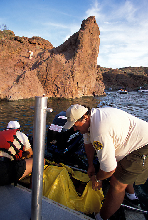 A man who drowned after jumping off the large rock in background into the water in Copper Canyon on Lake Havasu is pulled onto a sheriff dept boat. Multiple deaths on the lake are common during holiday weekends like Memorial Day.