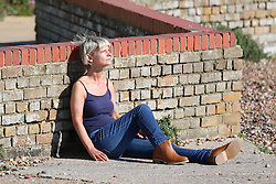© Licensed to London News Pictures. 05/10/2014. Brighton, UK. A lovely and warm day on Brighton Beach People relaxing and sunbathing on the beach. The weather is sunny and temperatures are expected to be 18C in Brighton and the South Coast. Photo credit : Hugo Michiels/LNP