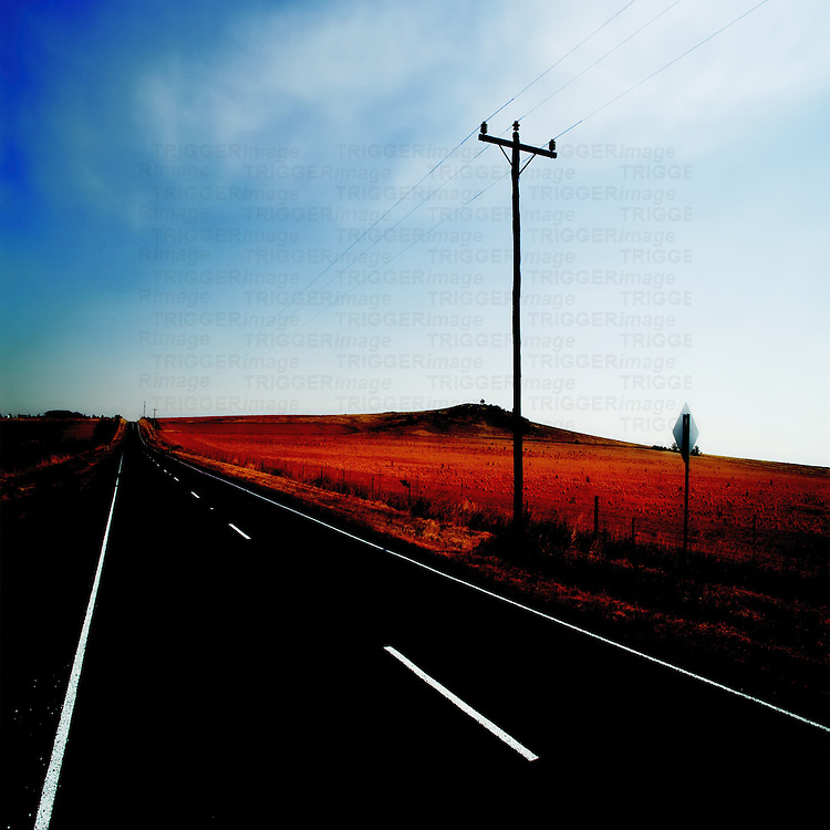 Long black road with telegraph pole