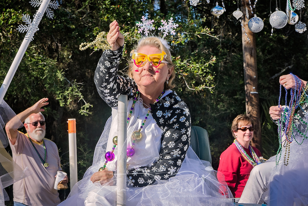 A member of the Dauphin Island Snowbirds throws beads in Dauphin Island's first People's Parade during Mardi Gras, Feb. 4, 2017, in Dauphin Island, Alabama. French settlers held the first Mardi Gras in 1703, making Mobile's celebration the oldest Mardi Gras in the United States. The first parade of the season is traditionally held on Dauphin Island and draws thousands. (Photo by Carmen K. Sisson/Cloudybright)